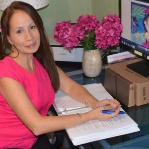August 2016 - Staff Member Elena Soto Sitting at er desk.